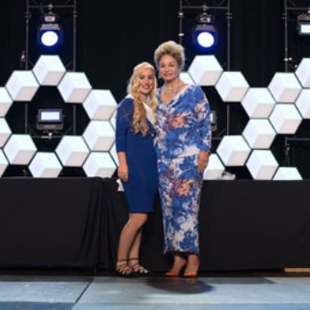 Marika and SeneGence founder Joni stand on stage during an awards ceremony.